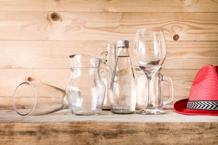 cruet: assorted glass bottles on a white washed wooden table. Clear glass bottles and containers of various sizes and shapes. Retro Style.