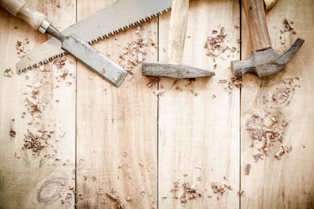 hammer and nails: carpenter tools,hammer,nails,shavings, and chisel on wooden background. Stock Photo