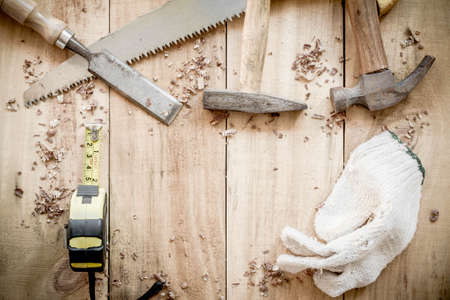 carpenter items: carpenter tools,hammer,meter,nails,shavings, and chisel on wooden background.