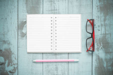convivencia escolar: Volver al concepto de escuela. libro abierto y l�pices en el fondo de madera.