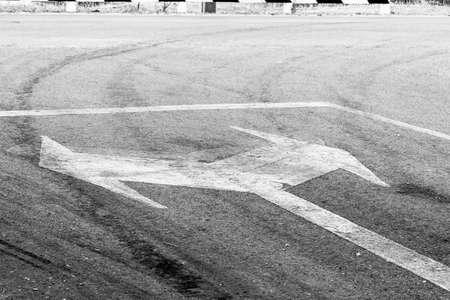 bidirectional: bidirectional arrow symbol on a wet asphalt road for the concept of choice.
