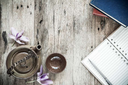 fireclay: Open Notebook and pen with Teapot on old wooden background. Stock Photo