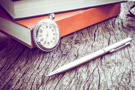 refinement: Pocket watch and book with pen, On old textured wood. Vintage style.