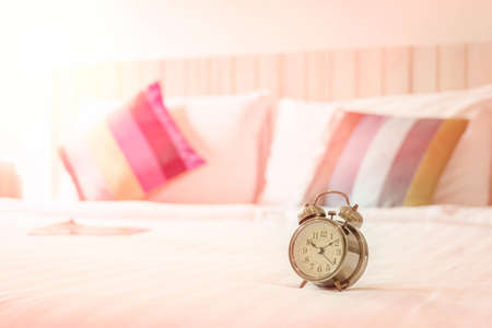 oversleep: close up view of alarm clock in morning bedroom environment.