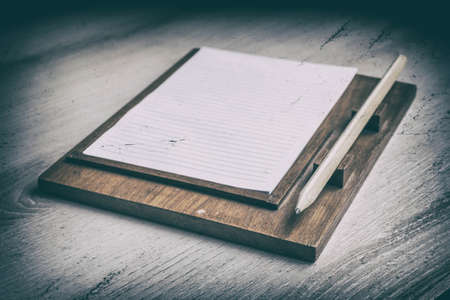 a literary sketch: paper notes with pencil on wooden table. Vintage style.