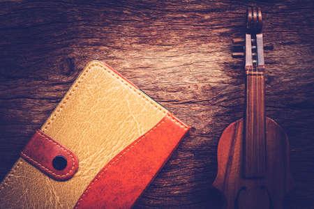 twelfth night: Violin and notebook on grunge dark wood background, Vintage style. Stock Photo
