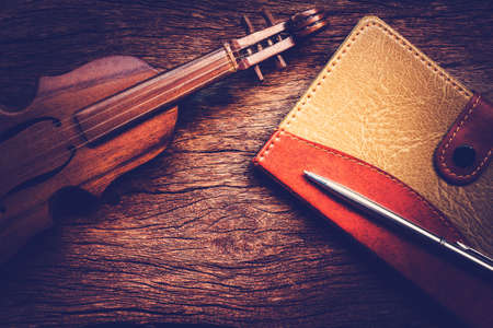 twelfth night: Violin and notebook with pen on grunge dark wood background, Vintage style.