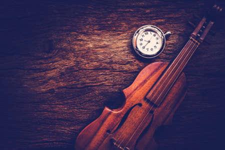 twelfth night: Violin and pocket watch on grunge dark wood background, Vintage style. Stock Photo