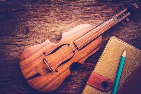 twelfth night: Violin and notebook with pencil on grunge dark wood background, Vintage style. Stock Photo