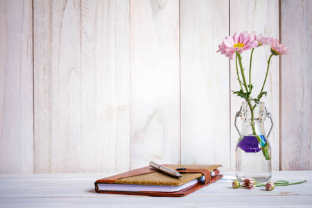 notebook or journal with pen of flowers arranged on a neutral white painted desk.