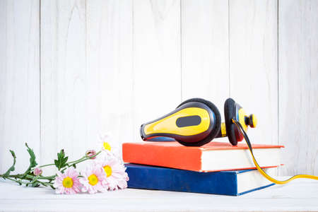 audio book: Headphones on books with Flowers on white wood background Stock Photo
