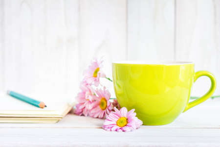 Notebook with a pencil on the table next to coffee and flowers. Stock Photo