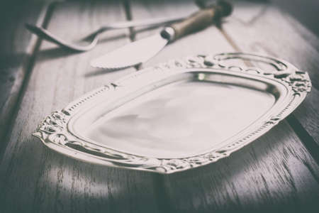 Vintage pewter plate, fork and knife on old dark wooden board Stock Photo