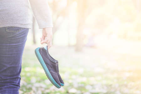 Woman holding black shoes in garden Stock Photo