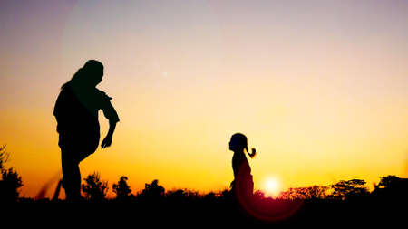 Silhouette happy family mother and daughter in the park at sunset with sun flare,Concept of friendly family and of summer vacation. Stockfoto