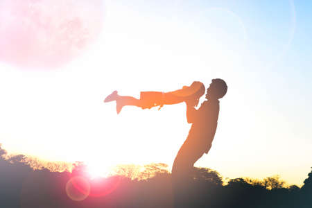 Silhouette of happy family father and child playing outdoors at sunset