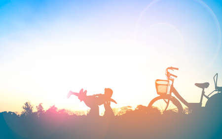 Silhouette of happy family mother and child playing outdoors at sunset Stockfoto