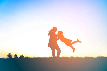 Silhouette of happy family mother and child playing outdoors at sunset Stock Photo
