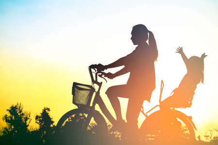 Silhouette of happy family mother and daughter with bicycle in the park at sunset with sun flare