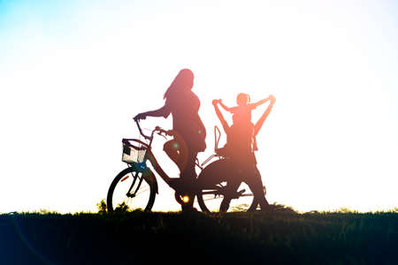 Silhouette of happy family father,mother and daughter with bicycle in the park at sunset with sun flare