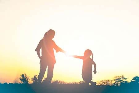 Silhouette of happy family mother and child playing outdoors at sunset 版權商用圖片