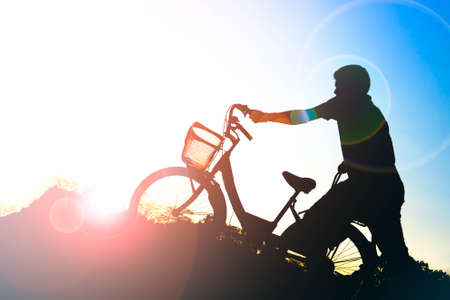 Silhouette of man with a bicycle in the park at sunset with sun flare