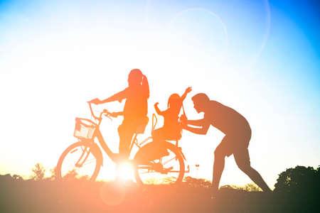 Silhouette de père de famille heureuse, mère et fille à vélo dans le parc au coucher du soleil avec lumière parasite Banque d'images - 71870801