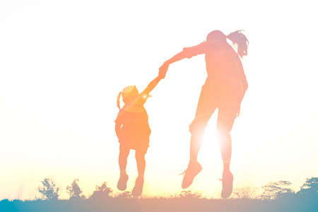 Silhouette of happy family jumping together on the park at sunset 版權商用圖片