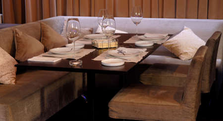 Table of a restaurant, waiting for visitors. Glasses, blanket , knife and a plate. photo