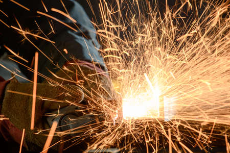 Industrial worker cutting and welding metal with many sharp sparks photo