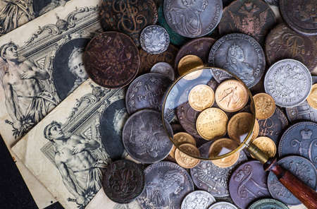 Gold and silver coins of the Russian Empire in the background kopyur.Antikvariat.