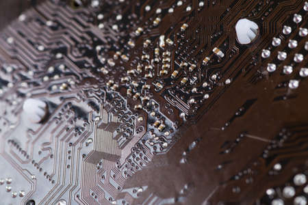 computer terminals: Macro closeup of a computer PCB using brown and black colors with silver soldered terminals
