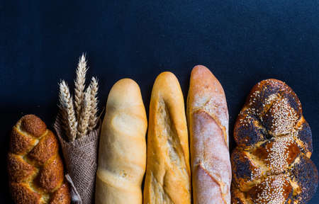 artisanal: Assortment of baked bread on wooden table background