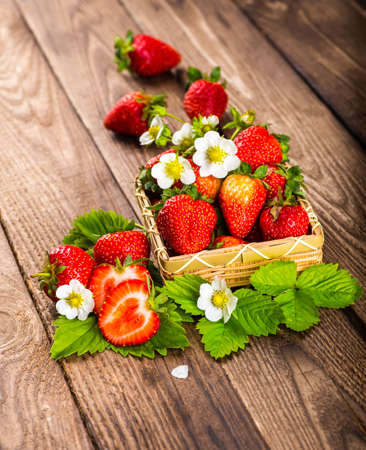 Strawberry on wood background. Strawberry with green leaves flower.
