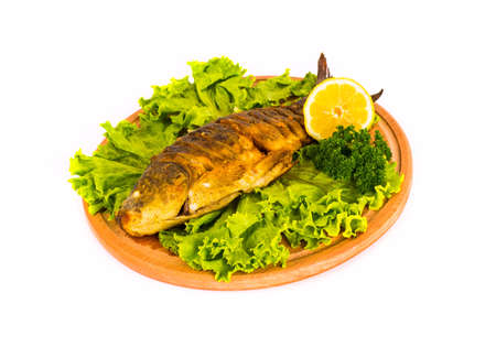 fish with lemon, parsley on kitchen board on a white background isolated