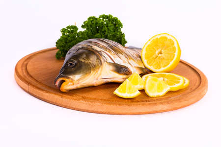 Fish with lemon and sauce on a board on a white background