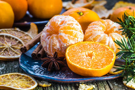 Ripe Mandarin fruit peeled open and place on old rustic look timber with group of mandarin fruits and leaves out of focus on the background Stock Photo