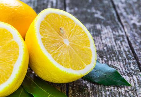 lemon wedge: Pile of lemons on wooden table Stock Photo