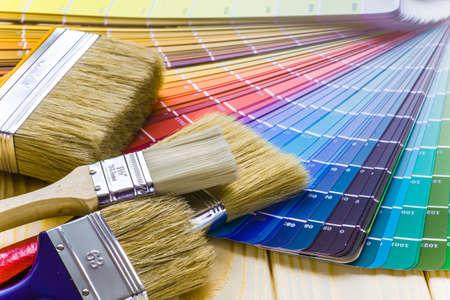 画家、家プロジェクト、色見本帳、ペイント ローラーとペイント ブラシとデコレータの作業テーブル