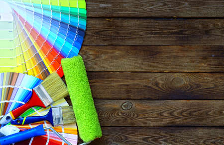 画家、家プロジェクト、色見本帳、ペイント ローラーとペイント ブラシとデコレータの作業テーブル 写真素材