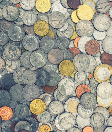 Coins of several currencies - background pattern.
