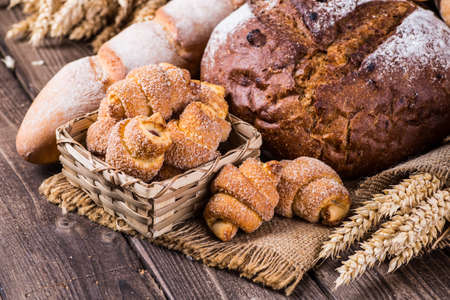 assortment of baked bread on wood table