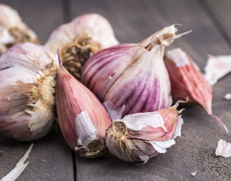 Organic garlic. Garlic press. Violet garlic.Wooden board. Stock Photo