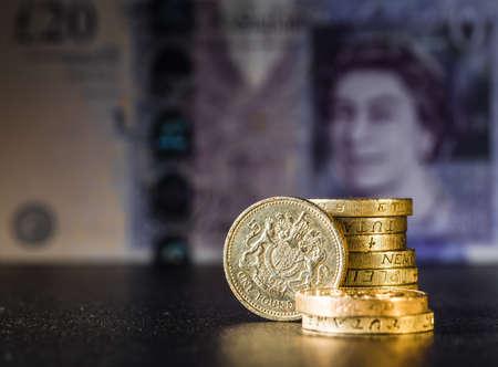 uk money: British coins stack on black, pound sterling