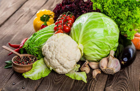 Fresh green garden cabbage on rustic wooden background. Vegetarian food. Assortment of fresh fruits and vegetables