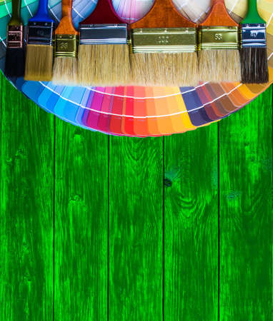 decorating: Painter and decorator work table with house project, color swatches, painting roller and paint brushes