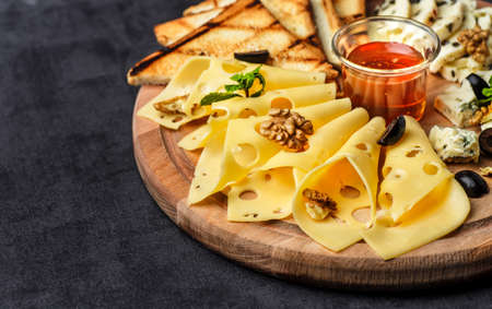 Cheese plate: Parmesan, cheddar, gouda, mozzarella and other with basil on wooden board on dark background with place for text.Honey and Crackers Stock Photo