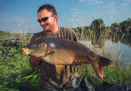 A happy angler holding a carp fish he caught Фото со стока