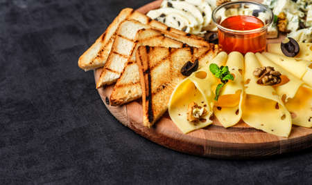 Cheese plate: Parmesan, cheddar, gouda, mozzarella and other with basil on wooden board on dark background with place for text.Honey and Crackers Фото со стока