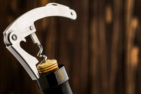 Bottle of wine with corkscrew on wooden background Фото со стока